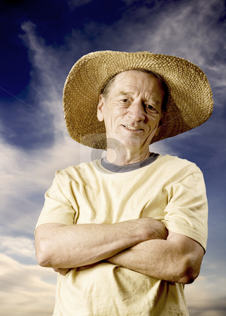 Man in a Big Straw Hat stock photo, Senior man in a straw hat in front of cloudy sky by Scott Griessel