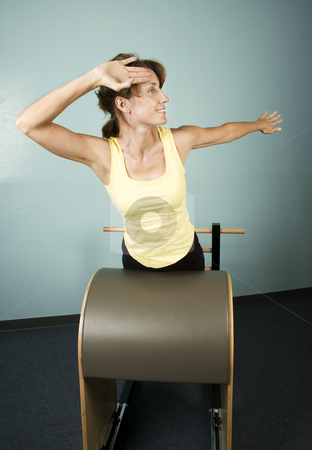 Woman Exercising stock photo, Athletic Woman Exercising and Stretching on Gym Equipment by Scott Griessel