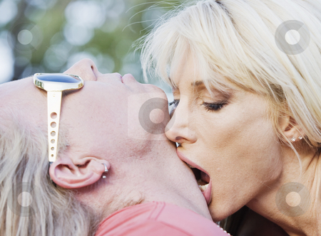 Rock and Roll Couple stock photo, Woman with big eyes kissing a man on the neck by Scott Griessel