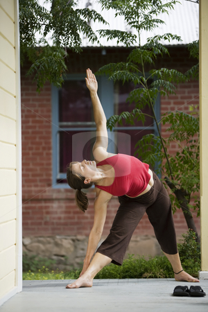 Yoga  triangle pose stock photo, Pretty Young Woman doing Yoga on a Porch by Scott Griessel