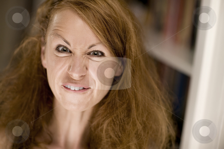 Woman making a funny face stock photo, Woman with big hair scrunching her face to make a funny expression by Scott Griessel
