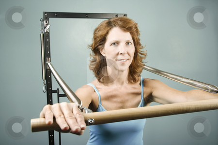 Woman doing a strength workout stock photo, Woman using gym equipment to do a strength workout by Scott Griessel