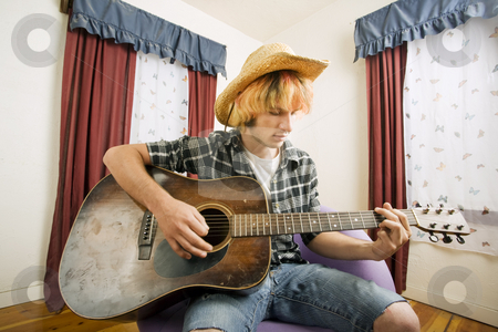 Young Guitar Player stock photo, Young musician with an old guitar in an empty room by Scott Griessel