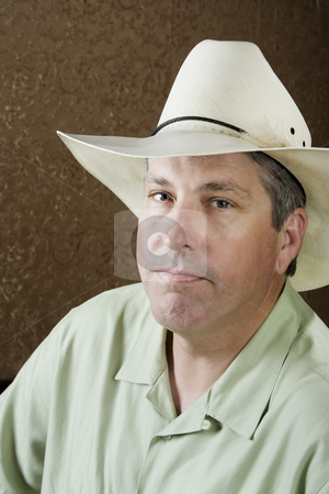 Man in a Cowboy Hat stock photo, Man wearing a white cowboy hat in front of a gold background by Scott Griessel