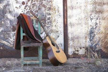 Acoustic Guitar Leaning on a Chair stock photo, Acoustic Guitar Leaning Against a Chair in a Rustic Setting by Scott Griessel
