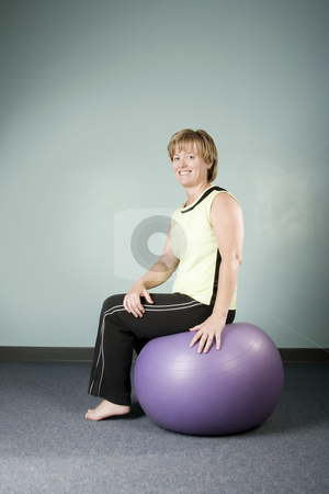 Woman Sitting on an Exercise Ball stock photo, Portrait of a Pretty Woman Sitting on an Exercise Ball by Scott Griessel
