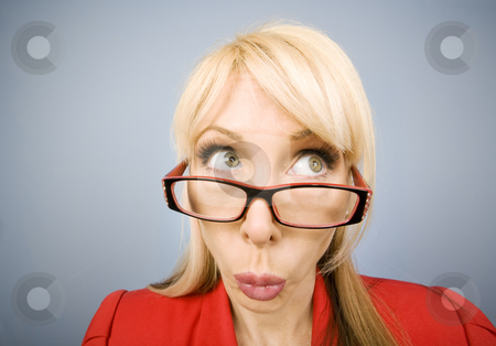 Woman in red making a funny face stock photo, Woman in red pursing her lips and making a funny face by Scott Griessel
