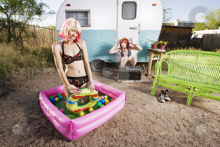 Trailer Girls stock photo, One girl makes a rude gesture towards her friend in a play pool by Scott Griessel