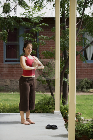 Yoga looking at camera stock photo, Pretty Young Woman doing Yoga on a Porch Looking Towards the Camera by Scott Griessel