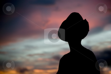 Woman in a cowboy hat silhouetted against a sunset sky. stock photo, Woman in a cowboy hat silhouetted against a colorful sunset sky. by Scott Griessel