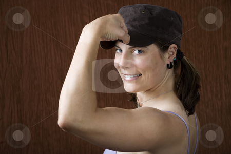Woman with blue eyes flexing her muscle stock photo, Closeup of woman with blue eyes wearing a cap flexing her bicep by Scott Griessel