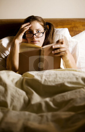 Woman Reading in Bed stock photo, Woman reading in bed with a shocked expression by Scott Griessel
