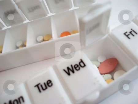 Drug dispenser stock photo, A weekly drug dispenser box with various pills inside by Stephen Gibson