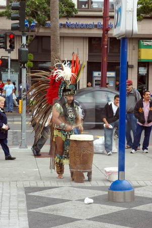 Aztec Street Performer stock photo, An Aztec street performer in full ceremonial dress plays a drum for dancers on a street corner in San Francisco California. by Lynn Bendickson