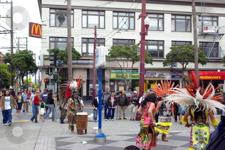 Aztec Street Performers stock photo, An Aztec street performers in full ceremonial dress plays a drum for women dancers on a street corner in San Francisco California. by Lynn Bendickson