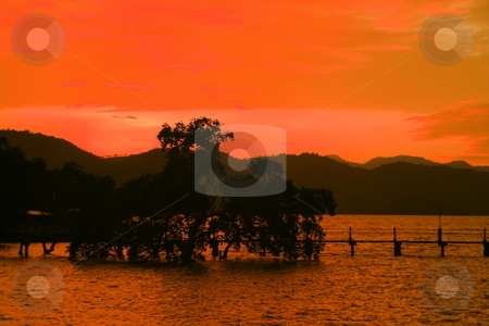 Orange sunset 2 stock photo, Orange sunset with silhouettes of mountain, trees and  bridge by Jonas Marcos San Luis