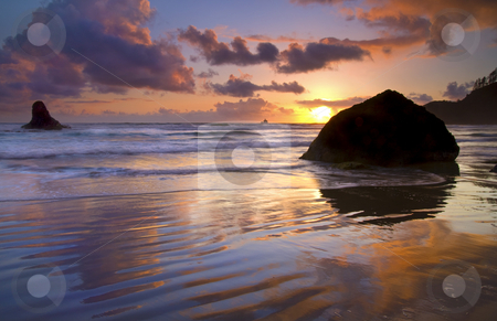 Ecola Sunset stock photo, Indian Beach ablaze in reflected color on the wet sand. Tillamook Rock lighthouse hides under the setting sun on the Horizon by Mike Dawson