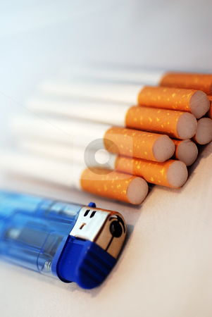 Cigarettes and Lighter stock photo, A photograph of a pile of cigarettes and a blue cigarette lighter by Philippa Willitts