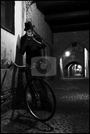 Smoker next to bicycle stock photo, This is a self portrait taken on an old street in Ferrara, Italy. by James Rose