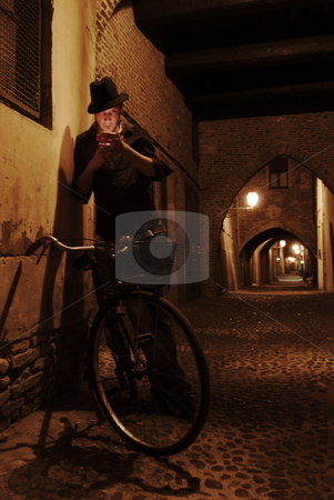Smoker next to bike stock photo, This is a self portrait taken on an old street in Ferrara, Italy. by James Rose