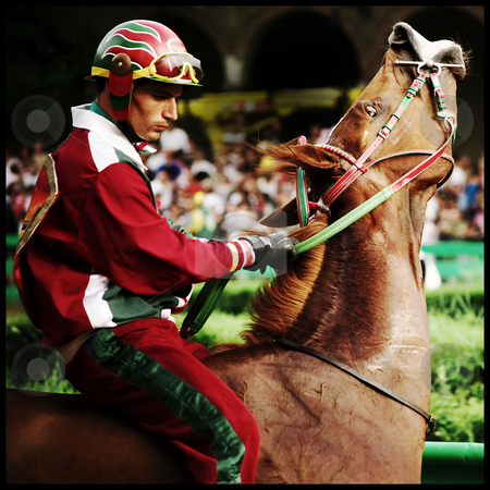 Racing Jockey on horse stock photo, Taken at the Ferrara Palio - a traditional horse race in similar to the more famous Siena palio. the jockey and horse are psyching up before the start of the race. by James Rose