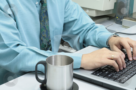 Working executive stock photo, Male executive  working on a laptop with tin cup on the side by Jonas Marcos San Luis
