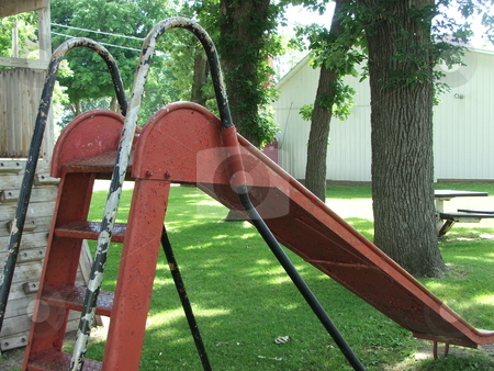 Old  Playground Slide stock photo, An old metal slide displaying multiple coats of paint is still enjoyed by young children in a small park playground in Chester, Iowa. by Dennis Thomsen