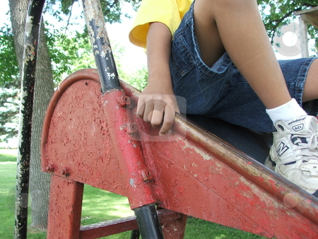 Old Playground Slide stock photo, A young boy prepares to slide down an old, well-used, metal, slide displaying a history of multiple coats of paint in a small park playground in Chester, Iowa. by Dennis Thomsen