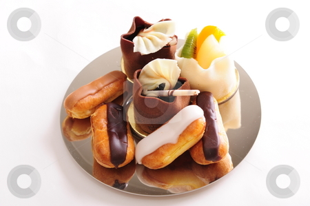 Fresh pastries stock photo, Delicious freshly baked eclairs and pastries on a shiny plate.  White background, not isolated. by Nicolaas Traut