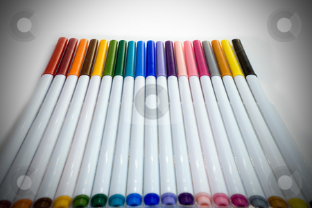 Colored Markers stock photo, Colored markers lined in a row with a darkening vignette by Richard Nelson