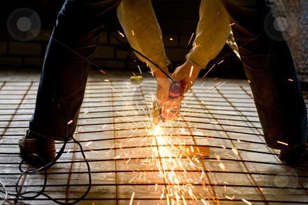 Construction worker with Angle Grinder stock photo, Construction worker cutting a construction net with an Angle grinder by Claudia Van Dijk