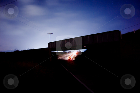Railroad Bridge Bathed in Moonlight stock photo, A car going under a railroad bridge in a cloudy night. by Peter Bruenner