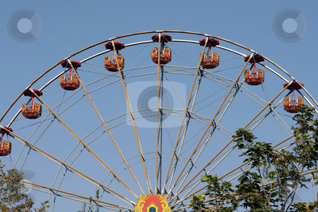Spinning weel  and trees stock photo, Big spinning wheel behind a tree at amusement park and blue sky background by EVANGELOS THOMAIDIS