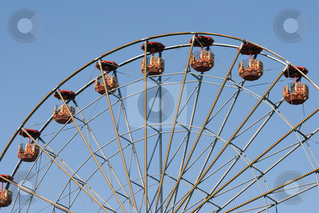 Spinning wheel stock photo, Big ferris wheel at amusement park and blue sky by EVANGELOS THOMAIDIS