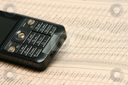 Cellphone and stocks stock photo, Black cellphone detail on financial newspaper business concepts by EVANGELOS THOMAIDIS