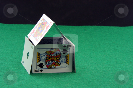 Playing cards house stock photo, House made of playing cards on green felt with copy space black by EVANGELOS THOMAIDIS