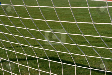 Goalpost net detail stock photo, Goalpost net detail with green grass blur in background sports concepts by EVANGELOS THOMAIDIS
