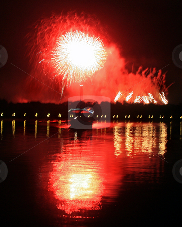 Fireworks stock photo, Fireworks with reflections in a lake and a boat. by Lucy Clark