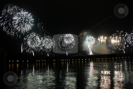 Fireworks stock photo, Long line of white or silver fireworks with reflections in a lake. by Lucy Clark
