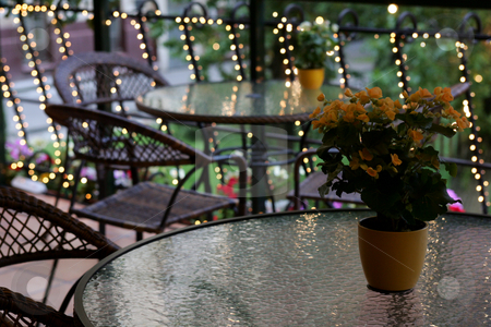 Flowerpot on glass table stock photo, Flowers on table in lighted patio area, romantic scene. by Martin Crowdy