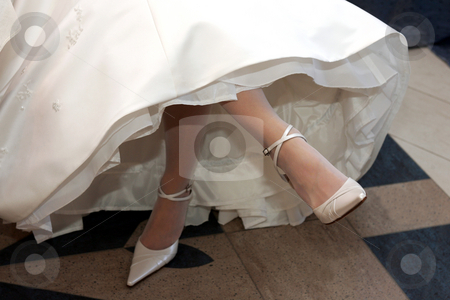 Bride's high heels stock photo, Bride in traditional white dress crossing her legs. by Martin Crowdy