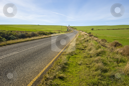 Deserted country-road running through green fields stock photo, A deserted country road running through some green fields. by Nicolaas Traut