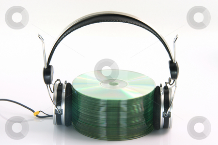 Headphones and cds stock photo, Headphones and pile of compact discs isolated on white background by EVANGELOS THOMAIDIS