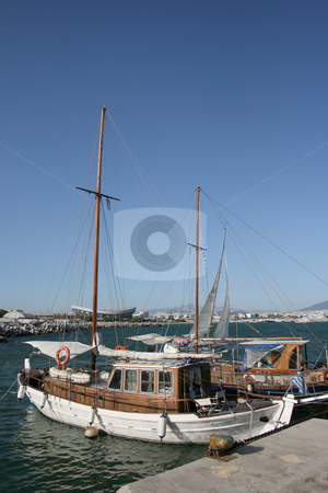 Two sail boats stock photo, Two sail boats at marina with athens city and stadium background greece vertical by EVANGELOS THOMAIDIS