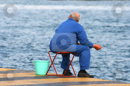 Man fishing stock photo, Senior man fishing at port dock in blue uniform by EVANGELOS THOMAIDIS