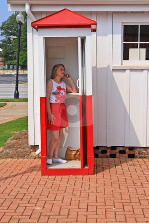 Cell Phone Booth stock photo, Woman using a cell phone in an  antique phone booth by Jack Schiffer