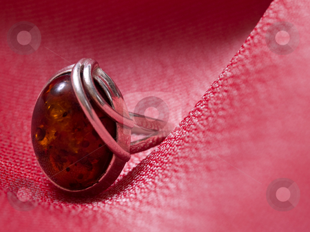 Amber ring pink silk stock photo, Amber ring on pink silk background by Adrian Costea