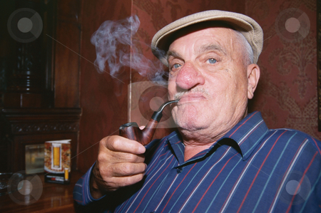 Elderly man smoking a pipe stock photo, Elderly man smoking a pipe by Mpixis World