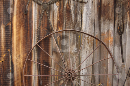 Horse Carriage Wheel stock photo, A metal horse carriage wheel against a barn wall. by Steve Stedman
