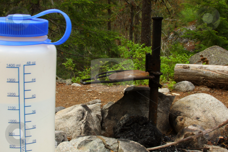 Campfire and Drink stock photo, Camping water bottle next to a camp fire pit in the forest. by Steve Stedman